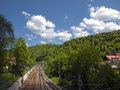 Railway in nature passing through a city the mountains Stock Photo
