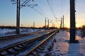 The railway in the rays of sunset frosty evening sun light stretching into distance rails Stock Photo