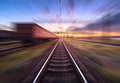 Railway station with cargo wagons in motion blur effect at sunse Royalty Free Stock Photo