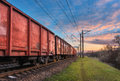Railway station with cargo wagons and train at sunset Royalty Free Stock Photo