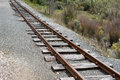 Railway track single with gravel and vegetation Royalty Free Stock Images