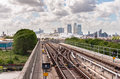 The railway tracks of docklands light railway with canary wharf skyscrapers in background Royalty Free Stock Image
