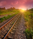 Railway tracks in sun raise moment with flare of sun Royalty Free Stock Photo