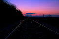 Railway tracks and sunset landscape against the backdrop of the line gauge to Royalty Free Stock Images