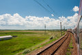 Railway and train go to horizon in green landscape under blue sky with white clouds cloudy scenic railroad Stock Images