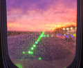Rain drops on airplane window seat view at sunset runway lights the background the Stock Image