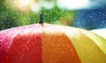 Rain drops falling onto umbella with rainbow colour Royalty Free Stock Photo