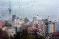 Rain drops falls on a window overlooking Auckland CBD New Zealan Royalty Free Stock Photo