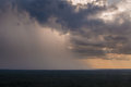 Rain pouring down from clouds at a distance storming falling on horizon with sun rays beams coming through in the Stock Photo