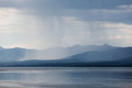 Rain shower over marsh lake yukon territory canda heavy canada and distant mountain range Stock Image