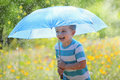 Rain and sunshine with a smiling boy holding an umbrella running through a meadow of wildflowers Stock Photos