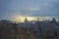 Rain on a window in an urban area with the distance out of focus with london during sunset Stock Image