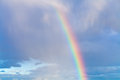 Rainbow in blue cloudy sky Royalty Free Stock Photo