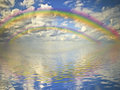 Rainbow, cloudy sky and ocean Royalty Free Stock Images