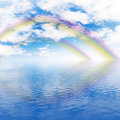 Rainbow, cloudy sky and ocean Royalty Free Stock Photo
