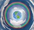 Rainbow encircled earth with circular clouds Stock Photo