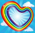 Rainbow heart in sky with clouds and sun. Abstract