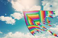 Rainbow kite flying in blue sky with clouds. Freedom and summer holiday Royalty Free Stock Photo