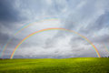 Rainbow landscape double across a stormy blue sky and farmer hayfield Royalty Free Stock Images