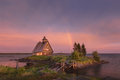 Rainbow on the lilac sky after a thunderstorm. Landscape of the White Sea with a small island, a wooden old house and a ruined bri