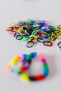 Rainbow loom bands and bracelets on a table Royalty Free Stock Photo