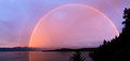 Rainbow over flathead lake full at sunset with mountains in the background Stock Photo