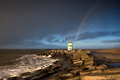 Rainbow over lighthouse and north sea ijmuiden netherlands Royalty Free Stock Image