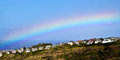 Rainbow over ocean view homes Stock Photos