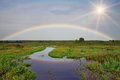 Rainbow over the river on sunset Stock Photography