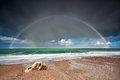 Rainbow over stone beach in atlantic ocean etretat france Stock Photos