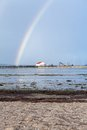 Rainbow over tidal mud flats at the coast beautiful colourful in colours of spectrum arcing with distant buildings Stock Photo