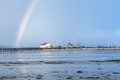 Rainbow over tidal mud flats at the coast beautiful colourful in colours of spectrum arcing with distant buildings Royalty Free Stock Photo