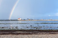 Rainbow over tidal mud flats at the coast beautiful colourful in colours of spectrum arcing with distant buildings Stock Image