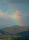 Rainbow over tree covered hills after a thunderstorm a shines in colorado Royalty Free Stock Photos