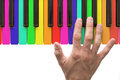 Rainbow piano keyboard with hand on white background Royalty Free Stock Photos