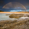 Rainbow with rock in foreground Royalty Free Stock Images
