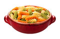 Rainbow rotini pasta isolated in a red bowl on a white background with a clipping mask Stock Photos