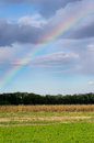 Rainbow on sky above farm land cloudy Stock Photo