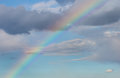 Rainbow on sky blue with grey clouds Stock Photos