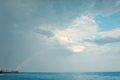 Rainbow in the sky delicate over sea on a cloudy Stock Photography