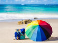 Rainbow umbrella and beach bag summer background with on the sandy Stock Image