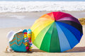Rainbow umbrella and beach bag summer background with white hat on the sandy Stock Images