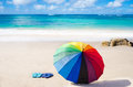 Rainbow umbrella and flip flops summer background with on the sandy beach Royalty Free Stock Image