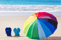 Rainbow umbrella and flip flops summer background with on the sandy beach Stock Photography