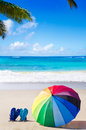 Rainbow umbrella and flip flops summer background with on the sandy beach Royalty Free Stock Images