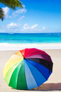 Rainbow umbrella summer background with on the sandy beach Stock Images