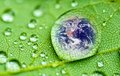 Raindrop planet earth inside a closeup on a green leaf elements of this image furnished by nasa Stock Photo