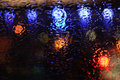 Raindrops on the glass over defocused street lights in night Stock Images