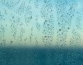 Raindrops on window of a ship at sea with horizon blue color ocean behind rain or spray drops cruise as the sun starts to rise Royalty Free Stock Images