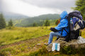 Raining in the mountains hiker with large backpack resting on a rock looking at rainy mountain landscape Stock Image